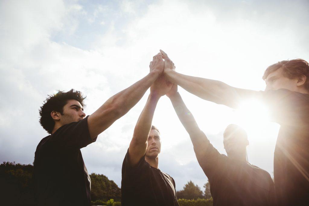 Vier Männer klatschen sich ab