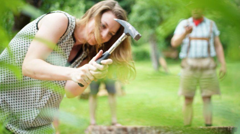 Frau schlägt einen Nagel in eine Baumscheibe